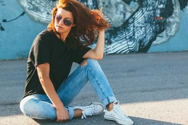Model wearing plain black t-shirt, boyfriend jeans, sneakers and hipster sunglasses posing against street wall